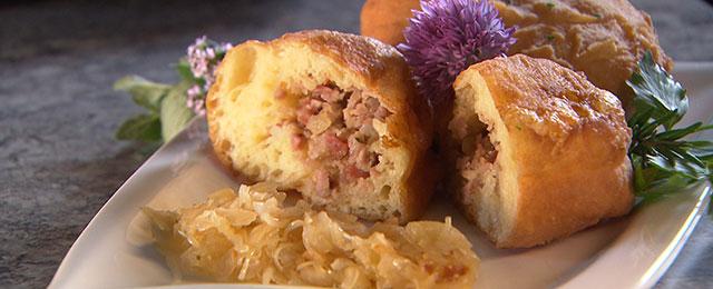 Fleischkrapfen auf Teller mit Sauerkraut
