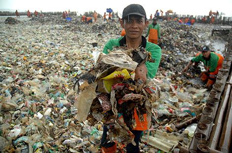 Mann inmitten von Müllbergen in der Bucht von Jakarta