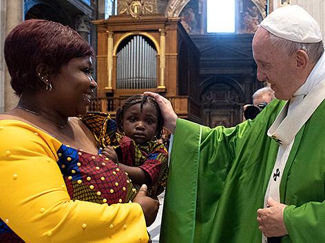 Papst Franziskus segnet ein Kleinkind im Rahmen einer Messe mit Flüchtlingen und Rettern