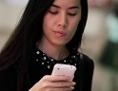 Eine Frau schaut beim Gehen konzentriert auf ihr Handy