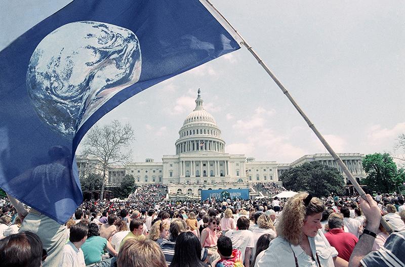 Menschen schwenken die Flagge des Earth Day vor dem Kapitol in Washington