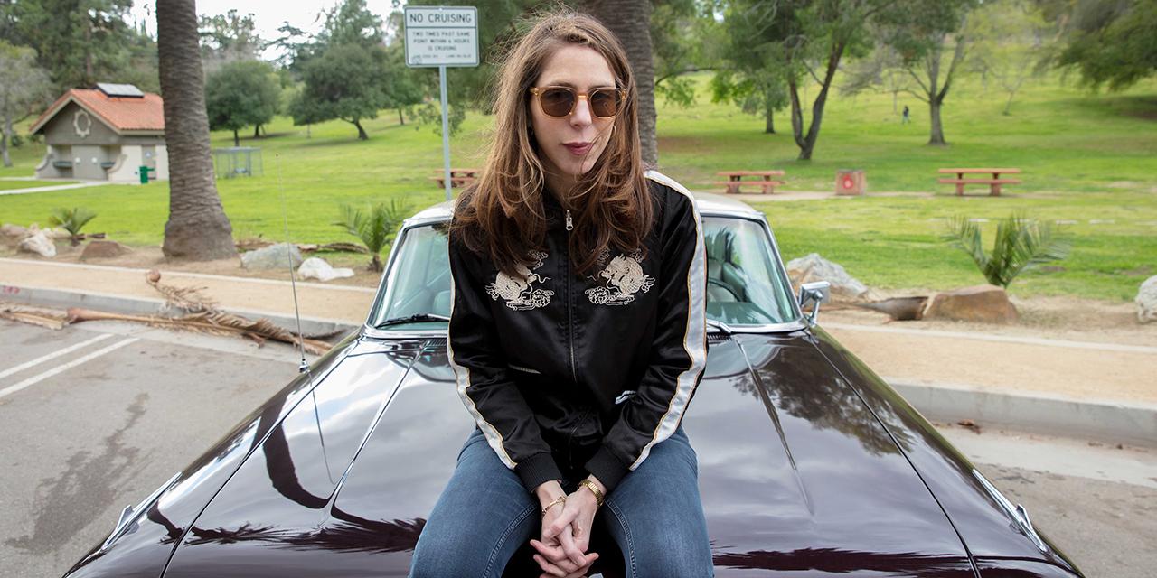 Rachel Kushner sitzt auf einer Motorhaube