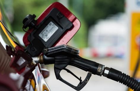 Ein Zapfhahn hängt im Tankstutzen eines Autos an der Tankstelle