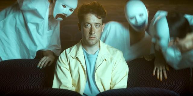 Mann sitzt im Kino, hinter ihm Gestalten mit lachenden und weinenden Masken