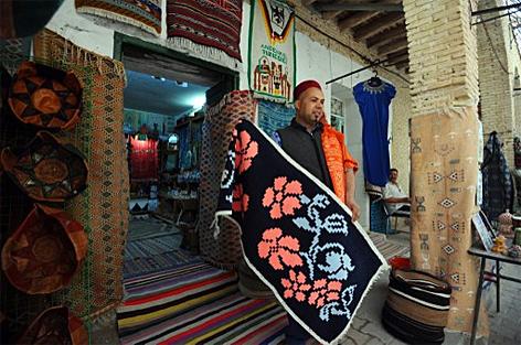 Ein Teppichhändler zeigt seine Waren am Markt in Tozeur im Süden von Tunesien