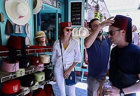 """Ein Tourist probiert die traditionelle tunesische Kopfbedeckung """"Chechia"""" an einem Marktstand in der Medina von Tunis"""