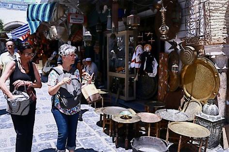Zwei Urlauberinnen mit Rucksack und Tasche schlendern an einem Marktstand in der Medina von Tunis vorbei