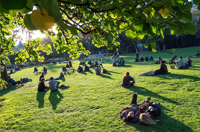 Stadtpark in Wien: Menschen sitzen auf einer Wiese und genießen die Sonne