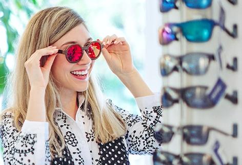 Eine junge Frau probiert bei einem Optiker eine Sonnenbrille