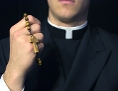 Junger Priester hält Rosenkranz in der Hand