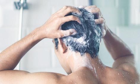 Ein Mann wäscht sich die Haare