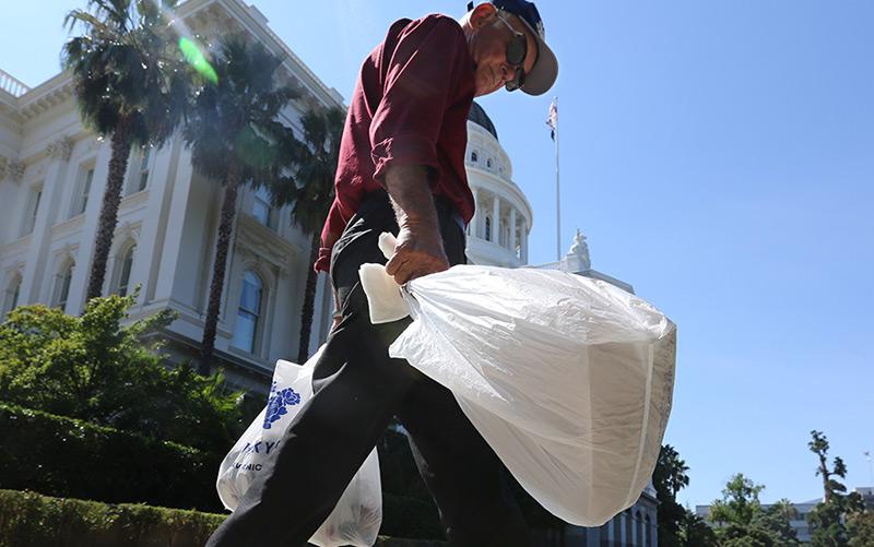 Ein Mann geht mit zwei Plastiksackerln in der Hand