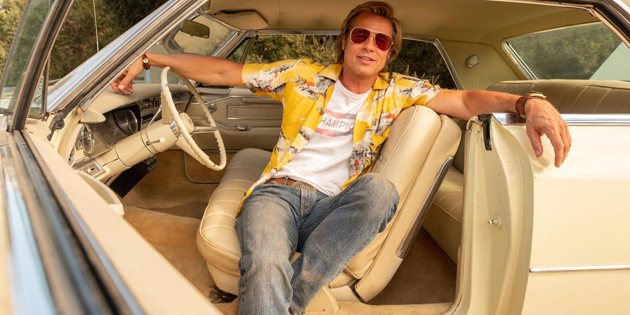Mann sitzt auf dem Fahrersitz eines Autos mit offener Wagentür