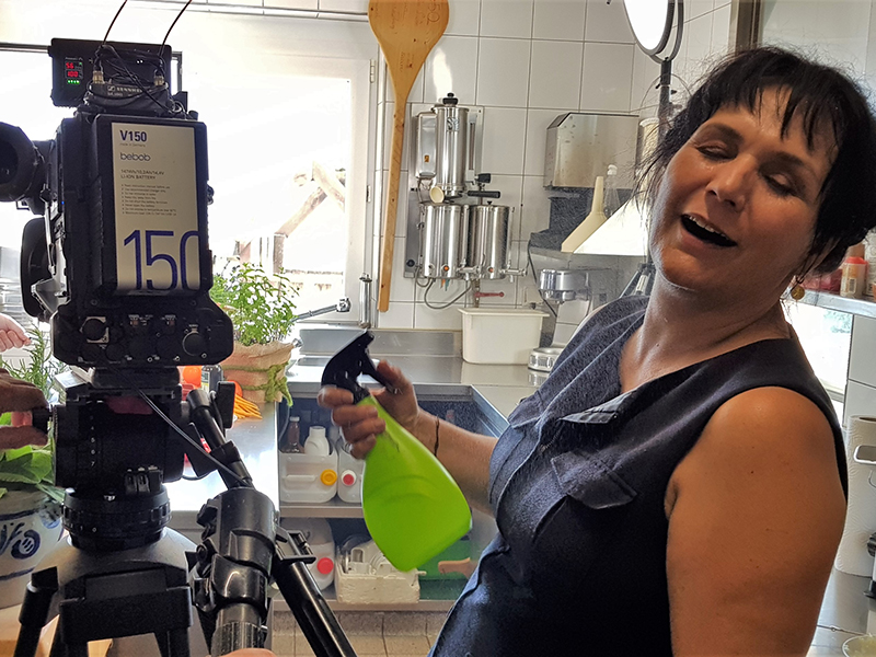 Frau besprüht sich in einer Küche mit einem Wassersprüher