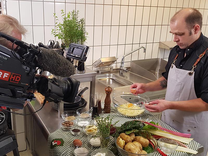 Ein Koch bereitet Essen zu, während ihn ein Kamermann dabei filmt.
