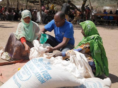 Ein Helfer der Hilfsorganisation Menschen für Menschen verteilt Lebensmittel