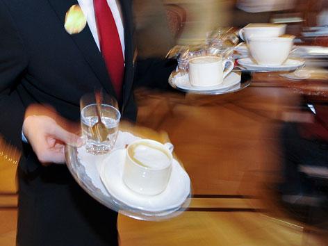 Ein Kellner trägt Tabletts mit Kaffeetassen