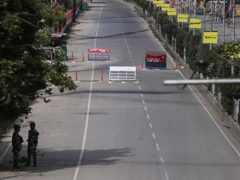 Eine leere, dreispurige Straße mit zwei Wachebeamten in Kaschmir