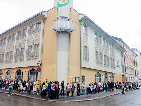 Menschen stehen in Solidarität mit Muslimen rund um ein Moscheegebäude in Oslo.