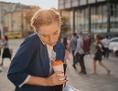 Frau im Kostüm mit eingeklemmten Telefon, Kaffeebecher und Unterlagen