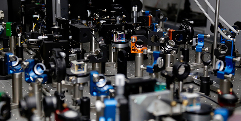 Versuchsaufbau: Labortisch mit Spiegeln, Linsen, Kabeln und Strahlenteilern