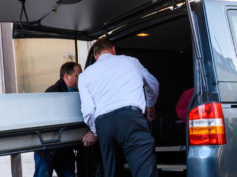 Ein Sarg wird in einen Leichenwagen hineingehoben
