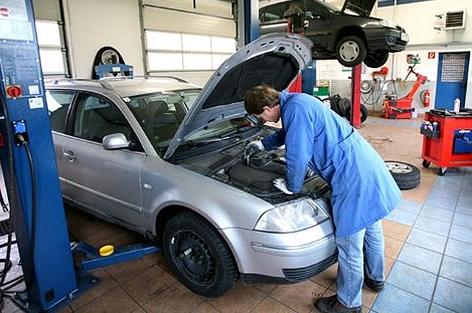 KFZ-Mechaniker bei der Kontrolle des Motorraumes in einer Werkstatt