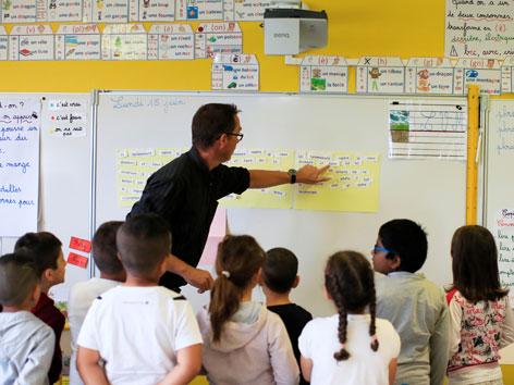 Ein Lehrer zeigt Kindern was an einer Tafel