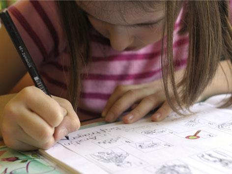 Ein Mädchen schreibt in ein Heft, die Haare hängen herunter