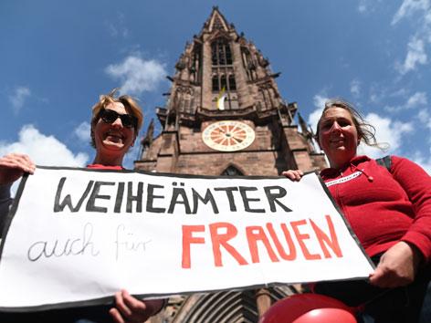Zwei Frauen mit einem Plakat mit der Aufschrift: Weiheämter auch für Frauen