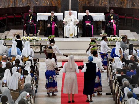 Papst Franziskus auf einem Podium vor Gläubigen in Mosambik.