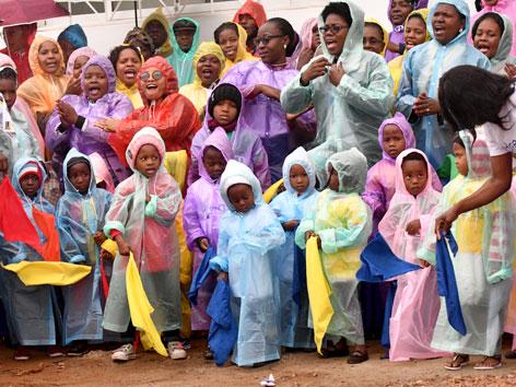 Kinder und Erwachsene in Regenmänteln vor einem Spital  in Mosambik. Sie warteten auf Papst Franziskus.