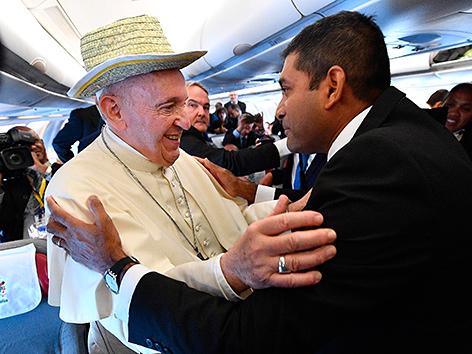 Papst Franziskus mit Hut und einem Journalisten auf dem Weg nach Maputo, Mosambik