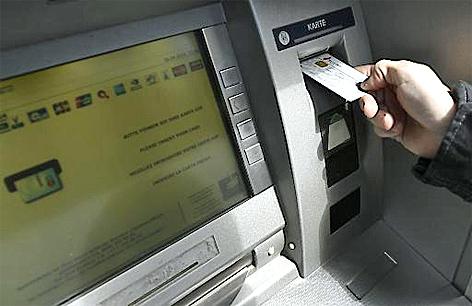Ein Person beim Abheben von Bargeld bei einem Bankomaten