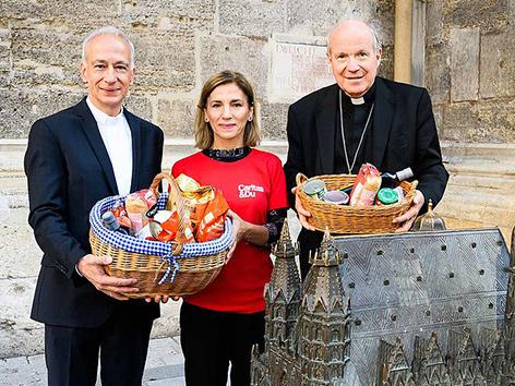 """Caritas-Präsident Michael Landau, eine Caritas-Mitarbeiterin und Kardinal Christoph Schönborn vor dem Wiener Stephansdom, Caritas-Projekt """"Lebensmittel und Orientierung"""" (Le+O)"""