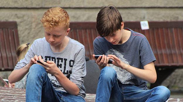 Zwei Jugendliche beim Handyspielen.
