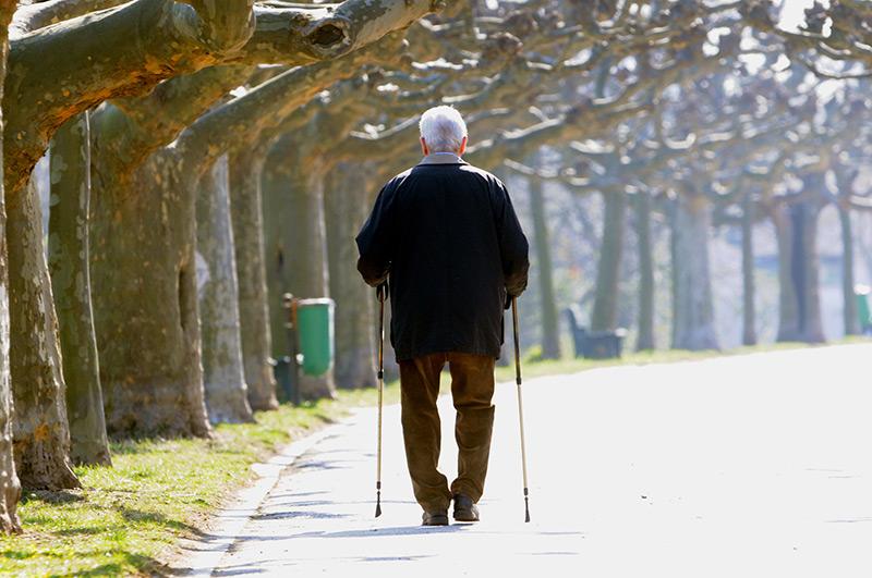 Ein älterer Mann spaziert mit Nordic-Walking-Stöcken