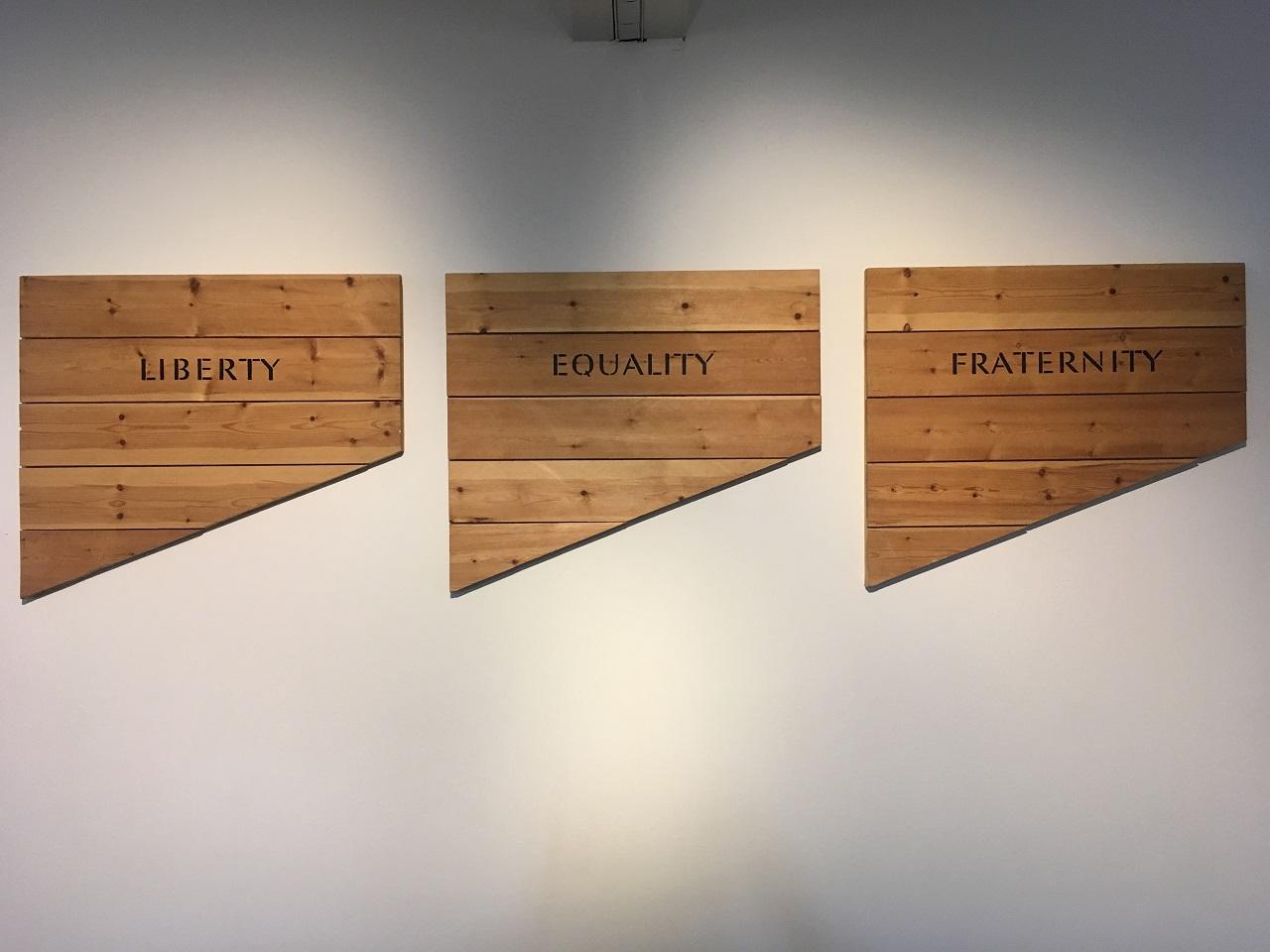 """Drei Holzbretterteile mit den Aufschriften """"Freiheit"""", """"Gleichheit"""", """"Brüderlichkeit"""" - eine Arbeit von Ian Hamilton Finlay"""