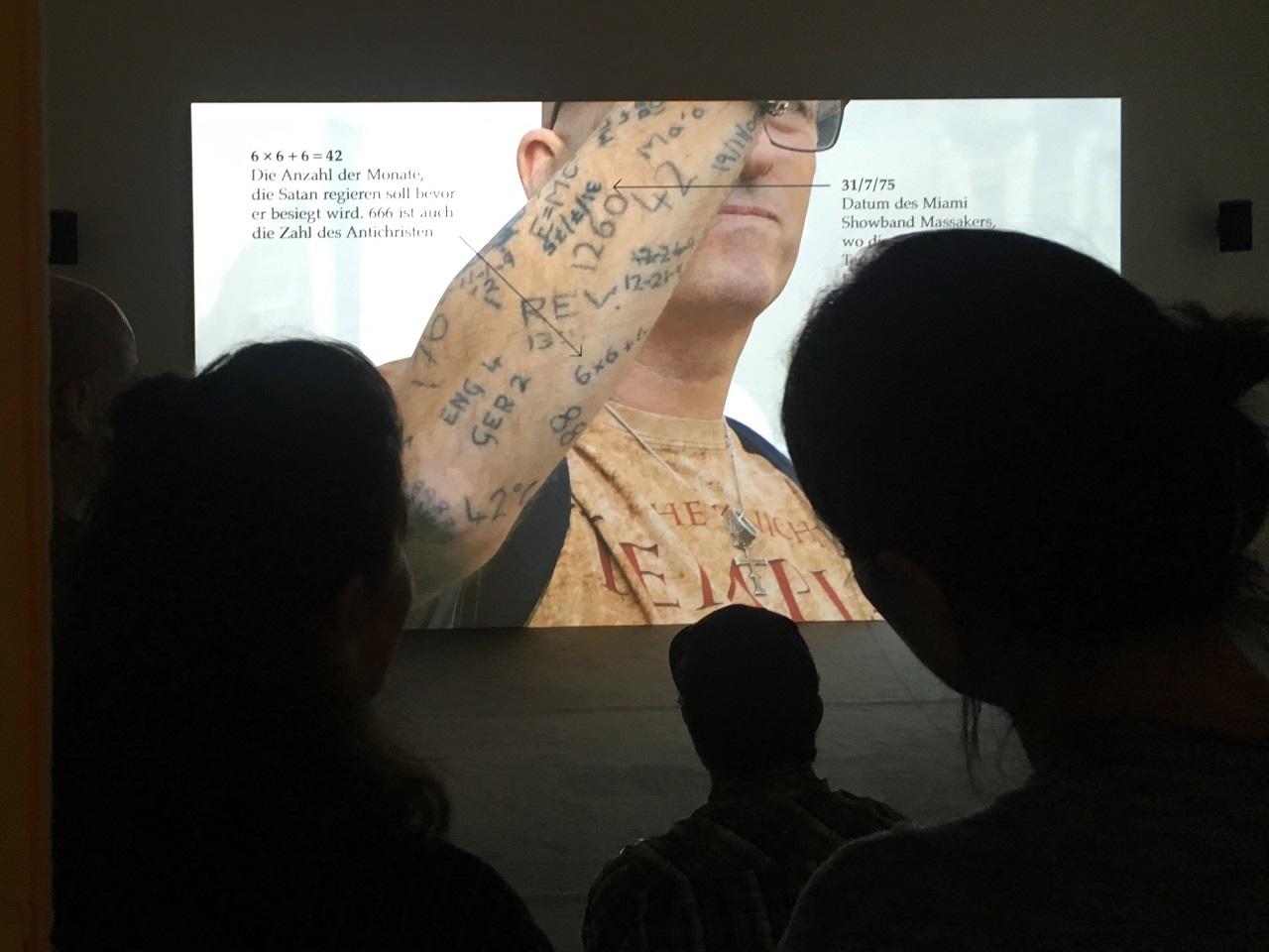 """BesucherInnen schauen Jeremy Dellers Film """"Putin's Happy"""" im Grazer Künstlerhaus"""