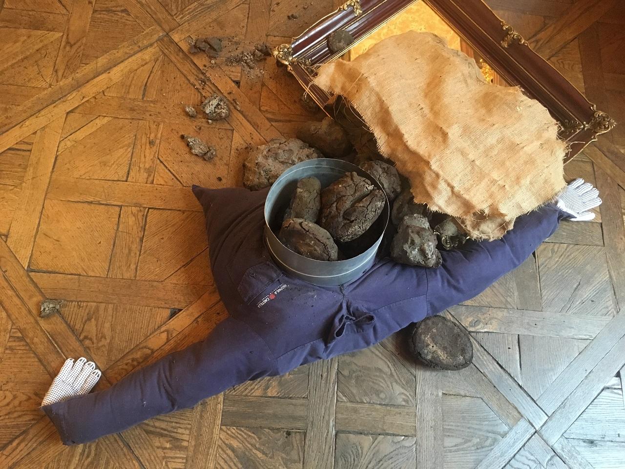 Materialien sind so am Parkett angeordnet, dass man denkt, einen verunfallten Arbeiter am Boden liegen zu sehen. Eine Installation von Oscar Murillo im Palais Attems in Graz.