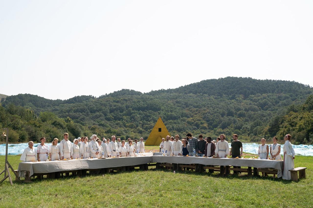 Lange Tafel mit weiß gekleideten Menschen