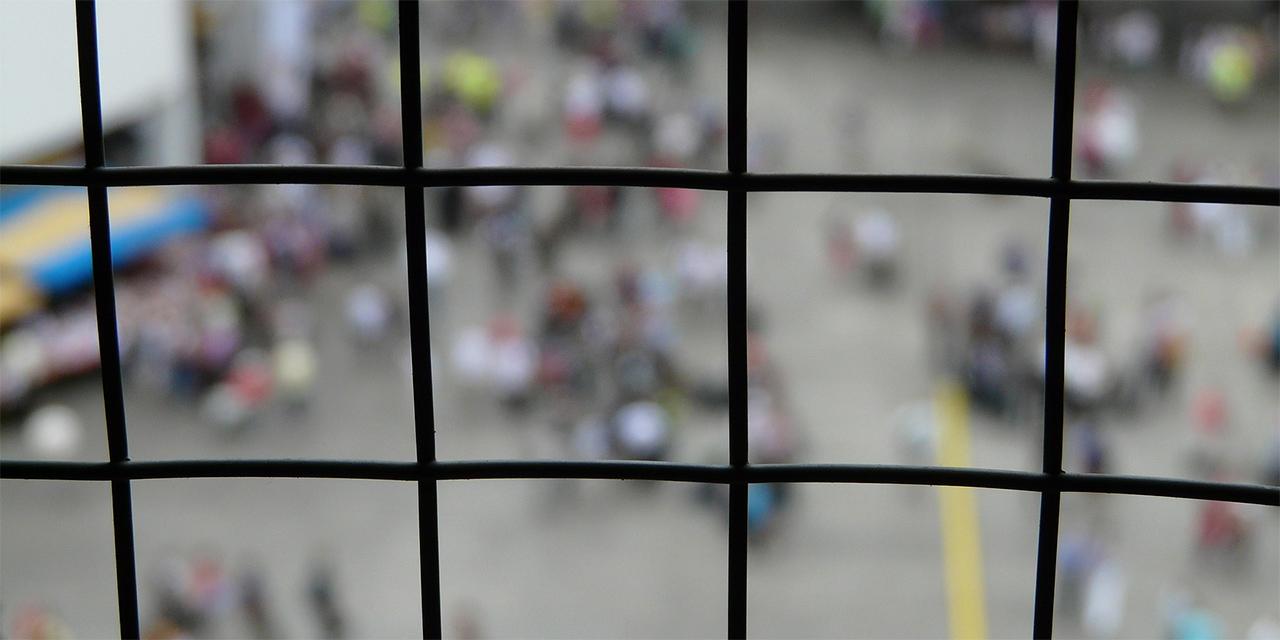 Blick durch Gitter auf einen Hof mit vielen Personen