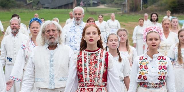 Viele Personen in weißen und bunt bestickten Kleidern