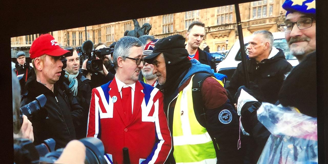 """Ein Filmstill aus Jeremy Dellers """"Putin's happy"""" zeigt eine Straßenszene in London, wo Brexitbefürworter und Gegner miteinander diskutieren"""