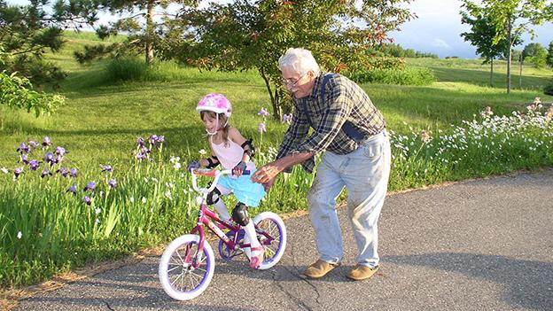 Opa lehrt seiner Enkelin Radfahren