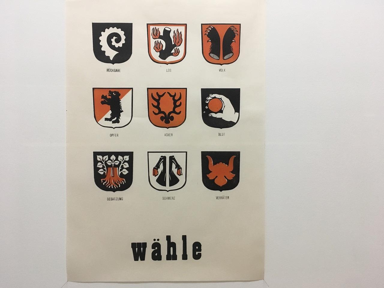 Ein Plakat des Künstlers Riccardo Giaconni ruft dazu auf, zu wählen und zeigt fiktive Wappen, die für Begriffe wie Schuld und Volk stehen