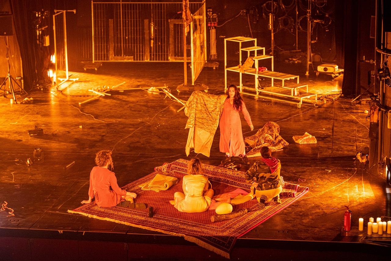 """Szene aus der Performance """"no apocalypse not now"""": Die Darstellerinnen haben sich eine Zuflucht auf einem Teppich eingerichtet."""