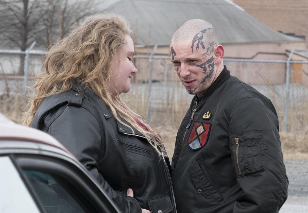 Eine Frau und ein tätowierter Mann stehen vor einem Auto