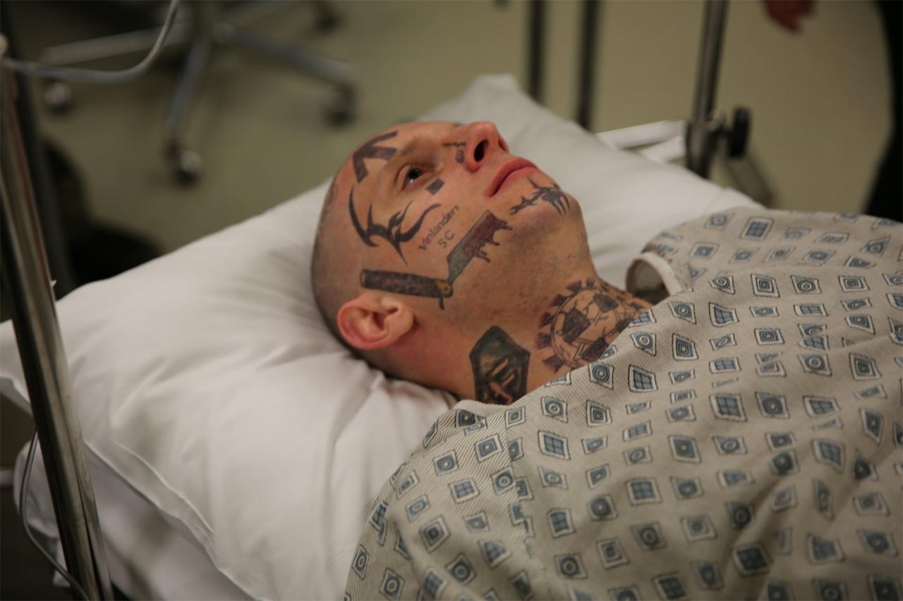 Ein tätowierter Mann liegt in einem Krankenhausbett