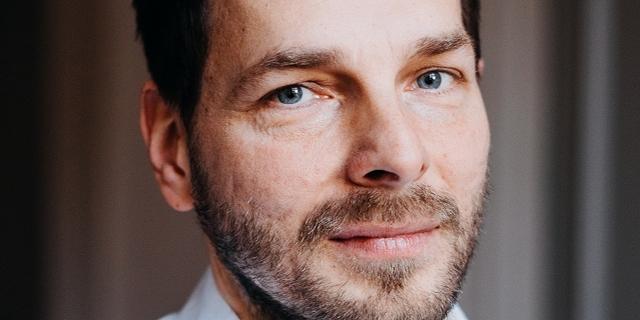 Der Autor Martin Beyer trägt ein Hemd und lächelt